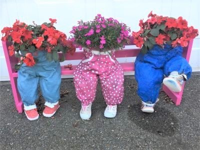 three concrete children on a bench decorated with flowers